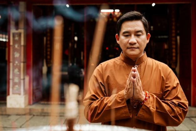 Vista frontale dell'uomo che prega al tempio con l'incenso