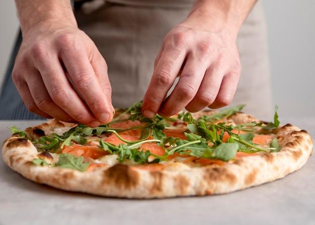 スモークサーモンのスライスと焼きピザ生地にルッコラを置く正面図の男