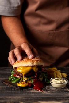 Front view man putting hand on burger