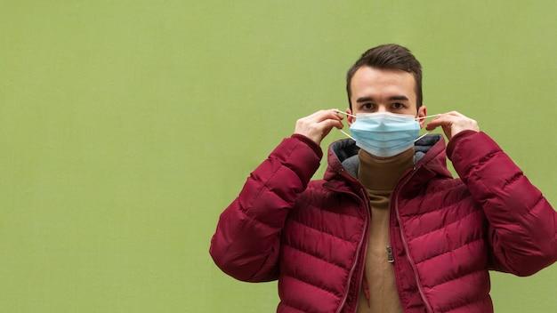 Vista frontale dell'uomo che mette sulla mascherina medica con lo spazio della copia