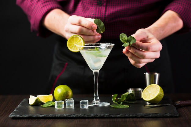 Front view of man putting mint on cocktail glass
