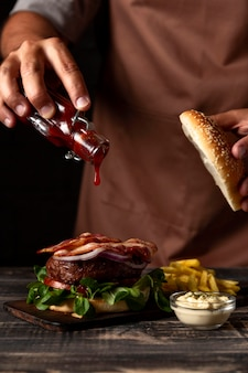 Front view man putting sauce on burger