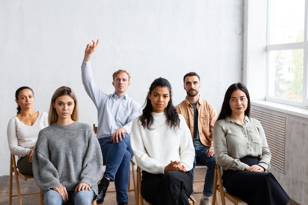 Front view of man raising hand for question at a group therapy session