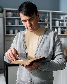 Vista frontale dell'uomo che legge dalla bibbia
