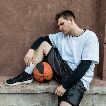 Front view man relaxing with a basketball