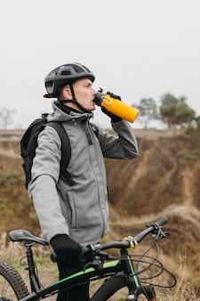 Vista frontale dell'uomo in sella a una bicicletta in montagna