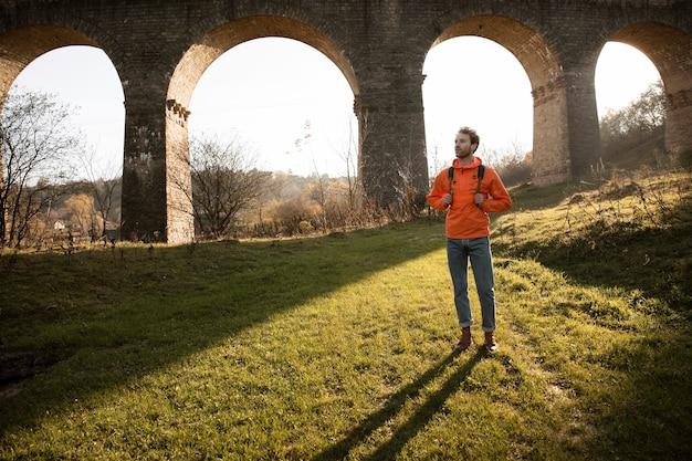 Vista frontale dell'uomo in un viaggio nella natura in posa accanto all'acquedotto