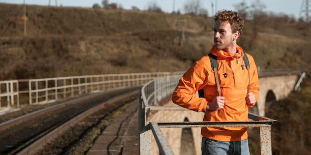 Vista frontale dell'uomo durante un viaggio su strada in posa accanto alla ferrovia