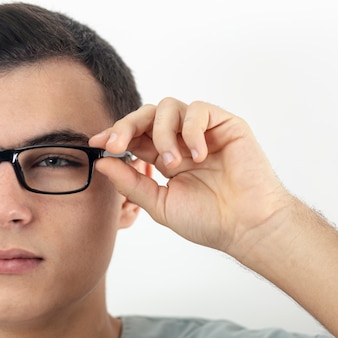 Front view of man's half face putting on glasses