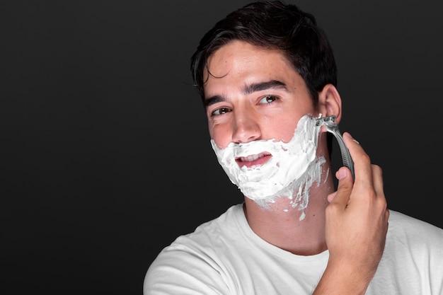 Front view man shaving beard