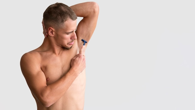 Front view of man shaving his armpit with razor