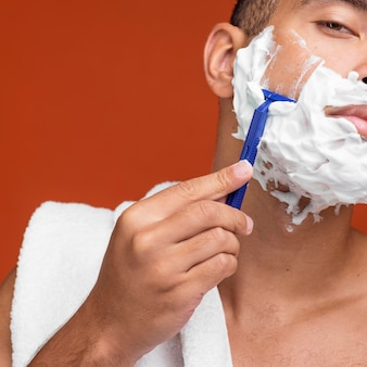 Front view of man shaving his beard with razor