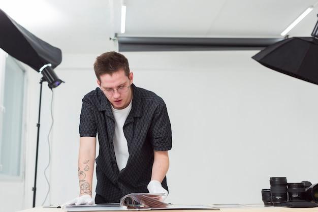 Vista frontale uomo in camicia guardando un album fotografico