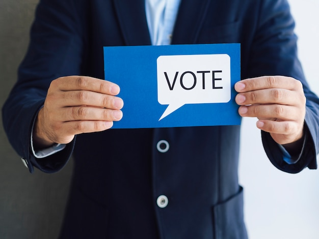 Front view man showing a voting card with a speech bubble