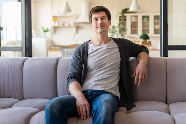 Front view of man sitting on couch