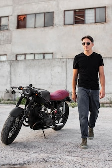 Front view man standing near motorcycle