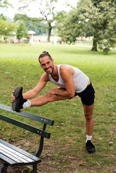 Front view of man stretching in park