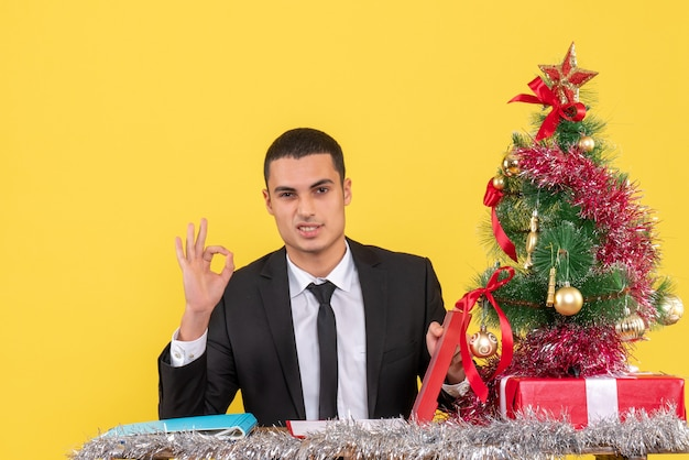 Front view man in suit sitting at the table holding document making okey sign xmas tree and gifts