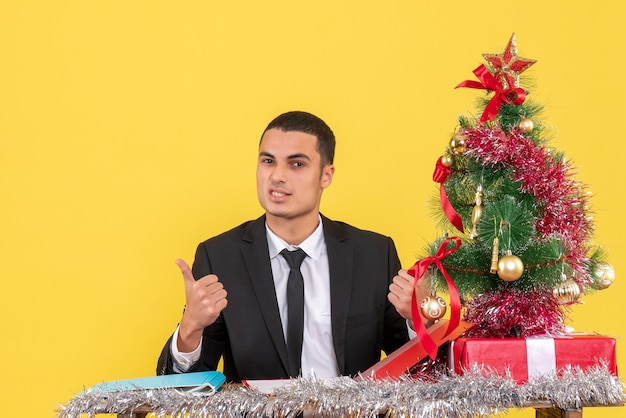 Front view man in suit sitting at the table holding document showing something xmas tree and gifts