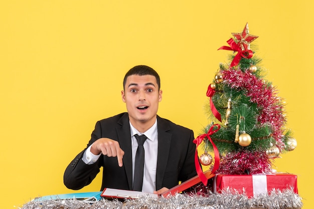 Front view man in suit sitting at the table pointing with finger document xmas tree and gifts