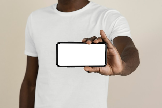 Front view of man in a t-shirt holding smartphone with copy space