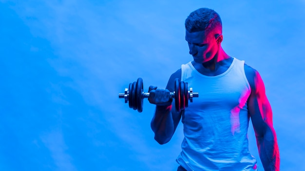 Front view of man in tank top holding weights with copy space