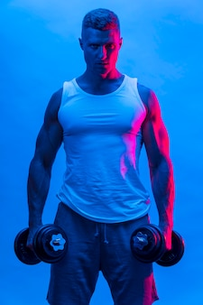 Front view of man in tank top holding weights