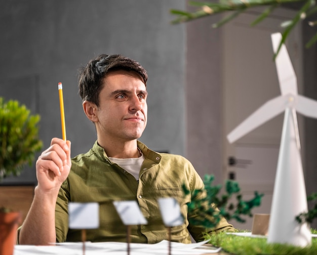 Front view of man thinking about an eco-friendly wind power project with wind turbines