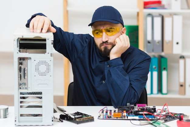 Front view man troubleshooting a computer