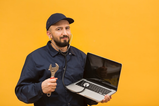 Front view man troubleshooting a laptop