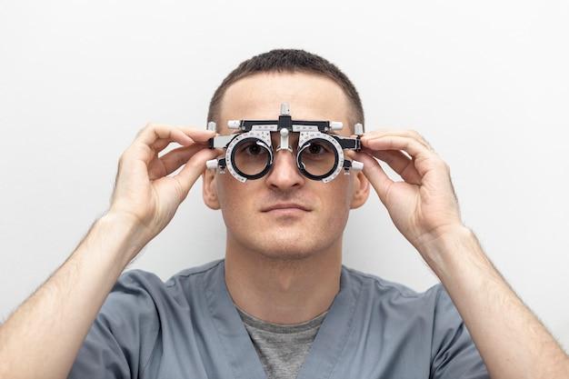 Vista frontale dell'uomo che prova sull'attrezzatura di ottica