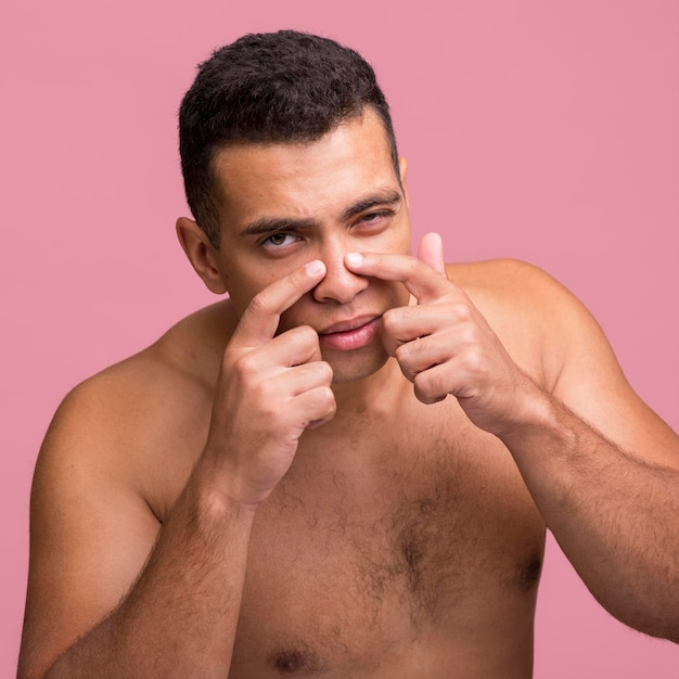 Front view of man trying to pop pimple on his nose