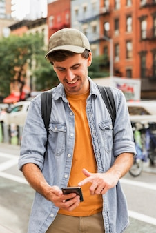 Человек вид спереди, используя мобильный телефон в городе