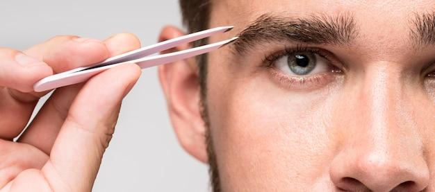Uomo di vista frontale utilizzando un paio di pinzette di close-up