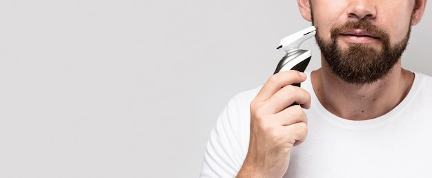 Front view man using a shaving machine with copy space