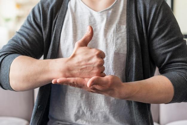 Vista frontale dell'uomo che usando il linguaggio dei segni