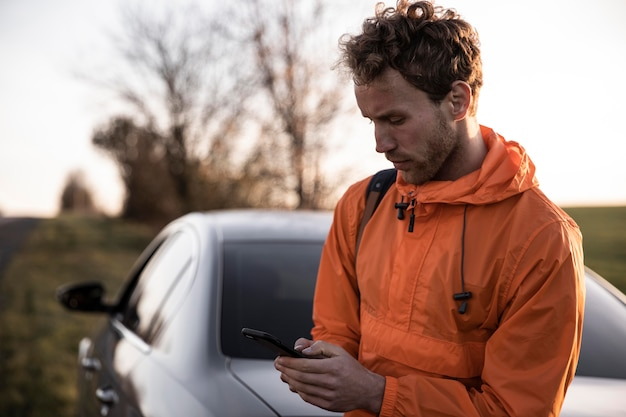Front view of man using smartphone outdoors while on a road trip