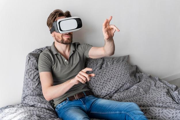 Vista frontale dell'uomo che utilizza le cuffie da realtà virtuale a letto