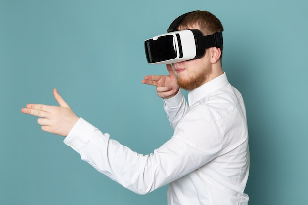 A front view man using vr in white t-shirt on the blue desk