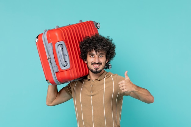 Front view man in vacation holding his big bag with smile on blue