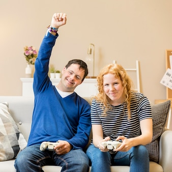 Front view of man victorious at playing video games against woman