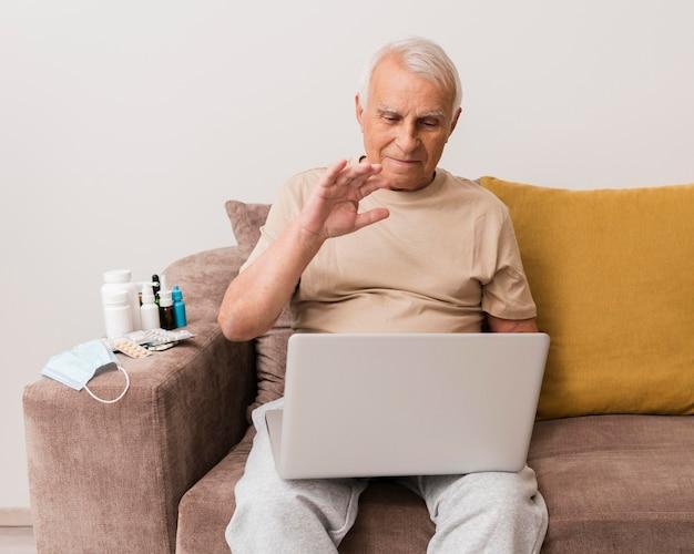 ノートパソコンで手を振っている正面図の男