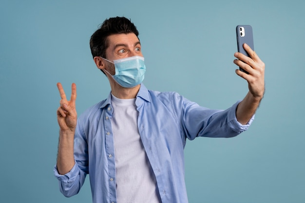 Front view of man wearing medical mask and taking selfie while making peace sign