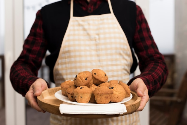 Front view of man with apron holding plate of muffins