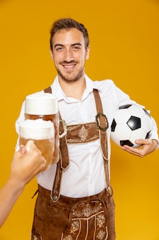 Front view of man with ball and beer pint