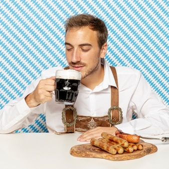 Front view of man with beer and sausages