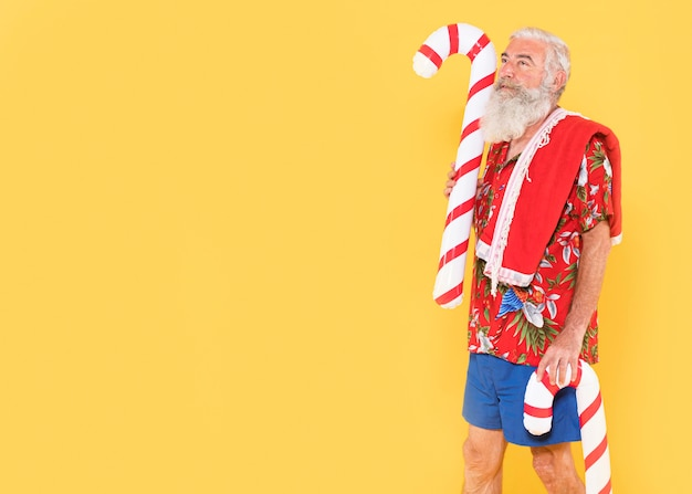 Front view of man with candy cane and copy space