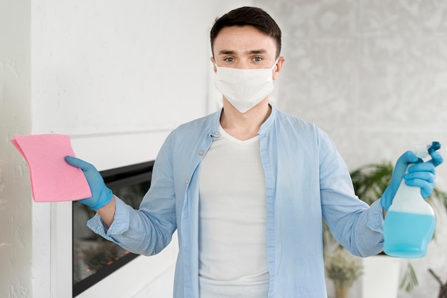 Front view of man with face mask holding cleaning liquid