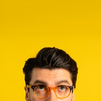 Front view of man with glasses looking up with copy space