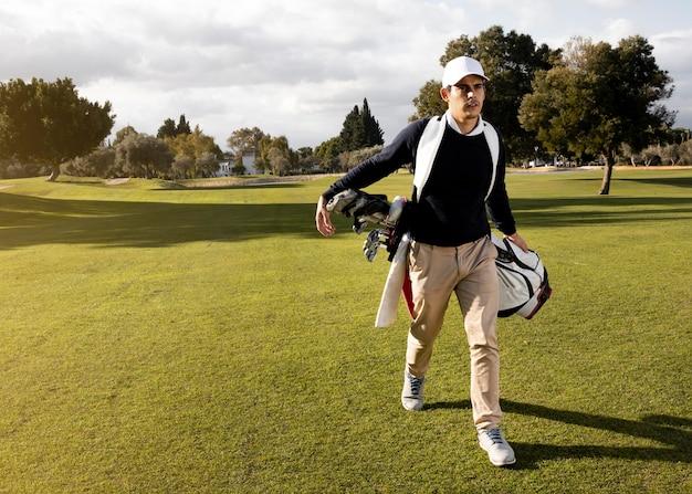 Vista frontale dell'uomo con mazze da golf sul campo